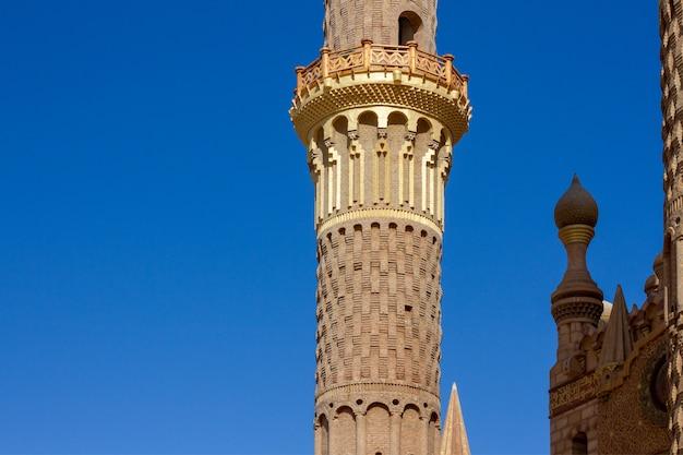 Vintage golden minaret on bright blue sky close-up. Premium Photo