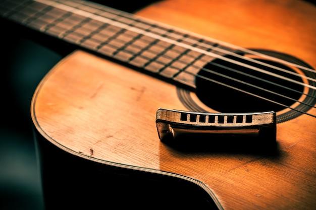 Vintage harmonica on acoustic guitar Premium Photo