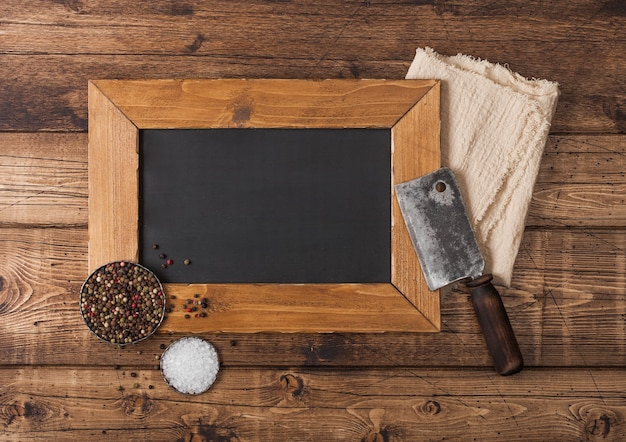 Vintage hatchet for meat with menu display board with salt and pepper on wooden background. Premium Photo