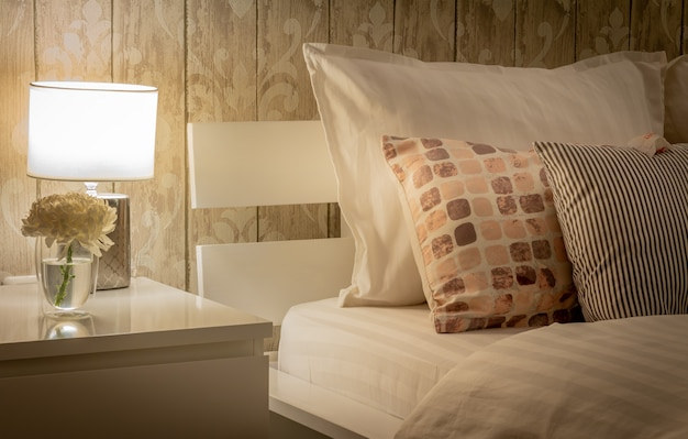 Vintage home interior with bedroom setting including bedside table with lamp. gray color scheme. satin finished style bedding Premium Photo