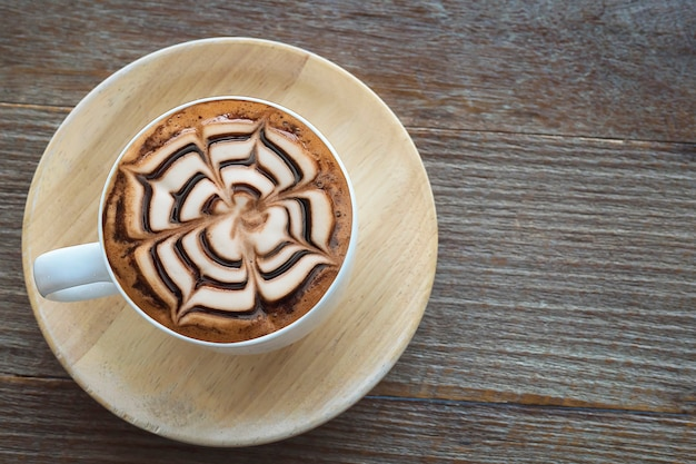 Vintage hot coffee cup with nice latte art decoration on old wooden texture table Free Photo