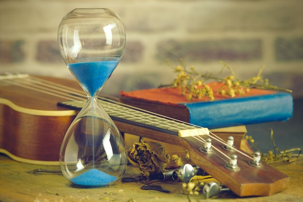 A vintage hourglass and ukulele with an old book and brass pen on a wooden table Premium Photo