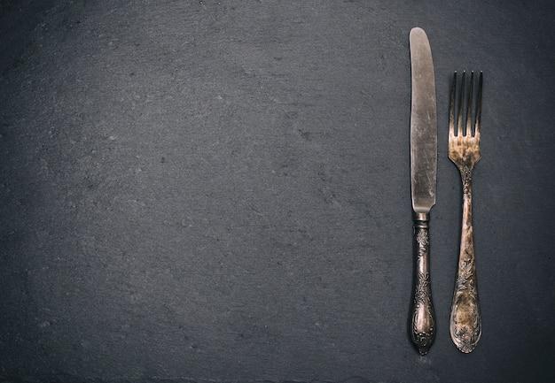 Vintage iron fork and knife on black Premium Photo