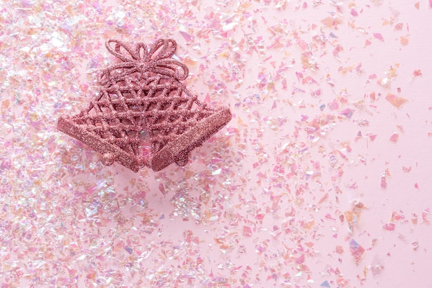 Vintage jingle bell on pink glitter . minimal christmas . happy new year. flat lay, top view, copyspace Premium Photo