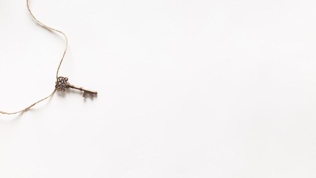 Старинный ключ висит на белом фоне Бесплатные Фотографии
