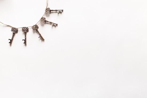 Vintage keys hanging on white background Free Photo