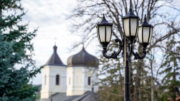 Lampione d'epoca con la chiesa in pietra e alberi. monastero di capriana, moldavia Foto Gratuite