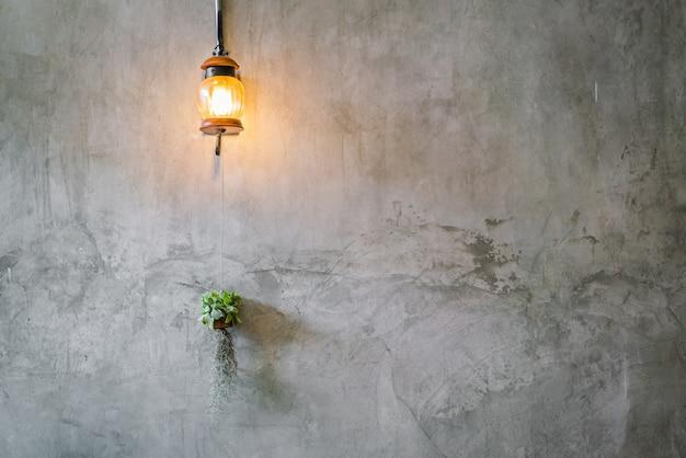 시멘트 벽 위에 식물 빈티지 조명 장식입니다. 무료 사진