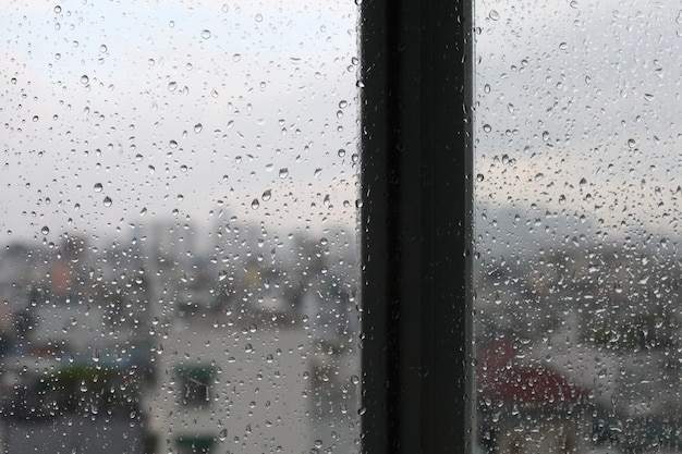 Vintage looking urban scene seen through a window in a rainy day Free Photo