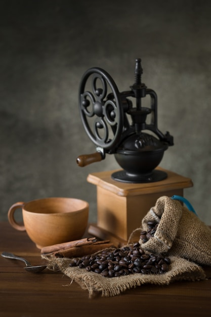 Vintage manual coffee grinder with coffee beans and cup Premium Photo