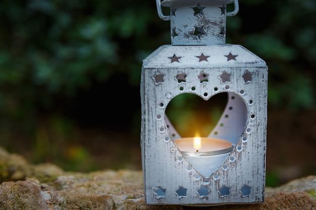 Vintage metal heart shape candle holder lit burning flame