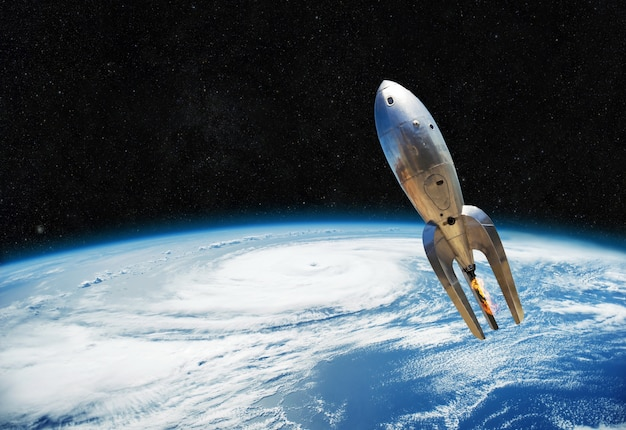 Vintage metal spaceship is flying near the earth. beginning of the space way Premium Photo