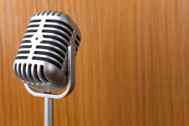 The vintage microphone close up image on wood background. Premium Photo