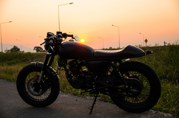 Vintage motorcycle cafe racer style with sunset scene Premium Photo