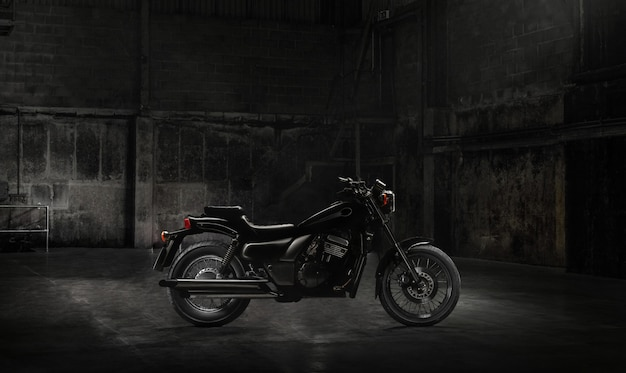 Vintage motorcycle standing in a dark building in the rays of sunlight. side view Premium Photo
