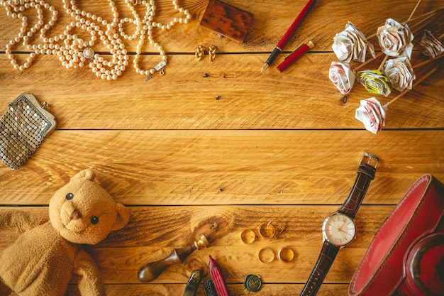 Vintage objects and jewelry in a wooden table with copy space in the middle. Premium Photo