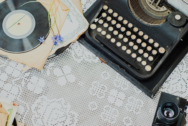 Vintage office desk with typewriter, stack of vinyl and camera on tablecloth Premium Photo