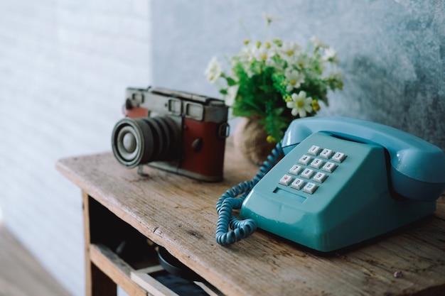 Vintage old telephone camera on wooden desk Premium Photo