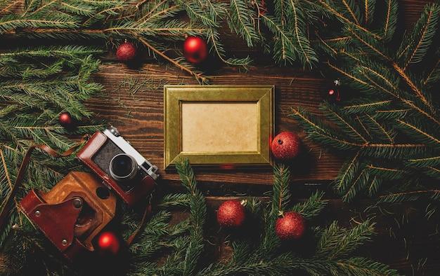 Винтажная фоторамка и фотоаппарат на столе рядом с рождественским украшением Premium Фотографии