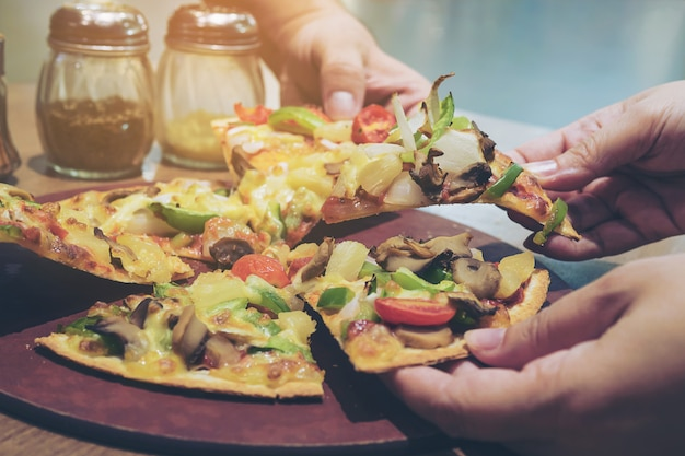 Vintage photo of pizza with colorful vegetable topping ready to be eaten Free Photo