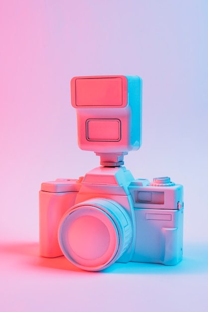 Vintage pink painted camera with lens against pink backdrop Free Photo