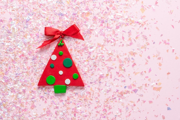 Vintage plasticine clay christmas tree on pink glitter . minimal christmas . happy new year. flat lay, top view, copyspace Premium Photo
