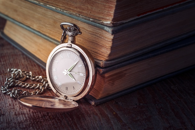 Vintage pocket watch on a chain and old books on a wooden background. Premium Photo