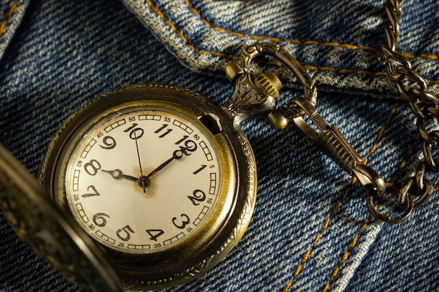 Vintage pocket watch is placed over an old blue denim shirt and the morning sun shines down in the top right corner. Premium Photo