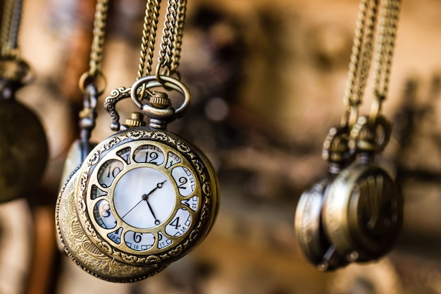 Vintage pocket watchs hanged with chains in an antique shop Premium Photo