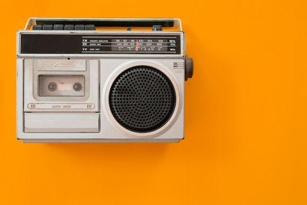 Vintage radio and cassette player on colour background, flat lay, top view, retro. Premium Photo