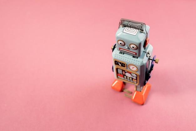 Vintage robot tin toy on pink background Premium Photo