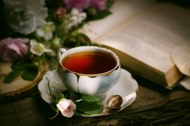 Vintage still life with an old porcelain tea cup, fresh little rose, snail and book. Premium Photo