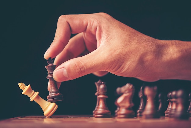 Vintage style image of a businessman with clasped hands planning strategy with chess Premium Photo