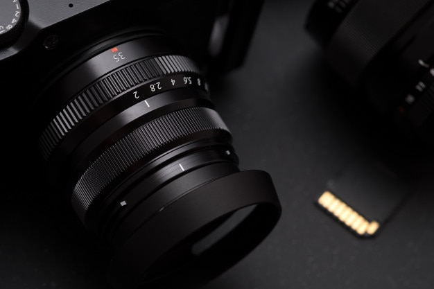 Vintage style mirrorless camera,concept of photographer. selective focus on lens Premium Photo