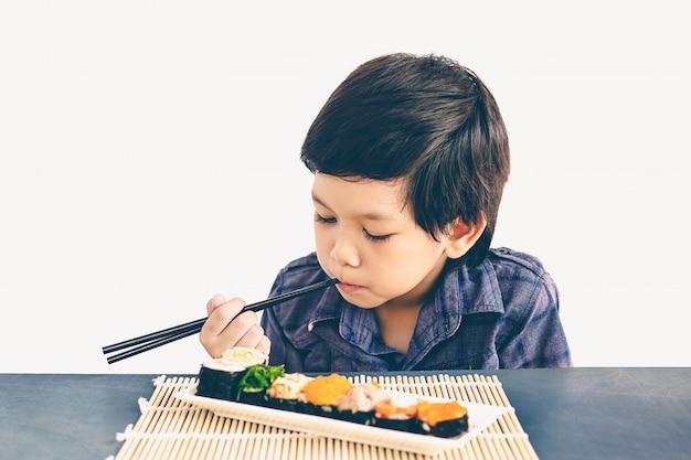 Vintage style photo of asian lovely boy is eating sushi Free Photo