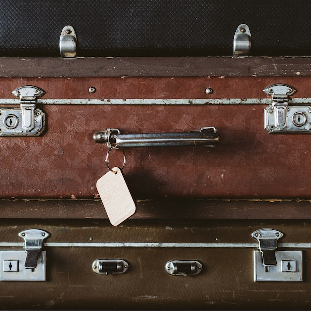 Vintage suitcases and wooden luggage tag. Premium Photo
