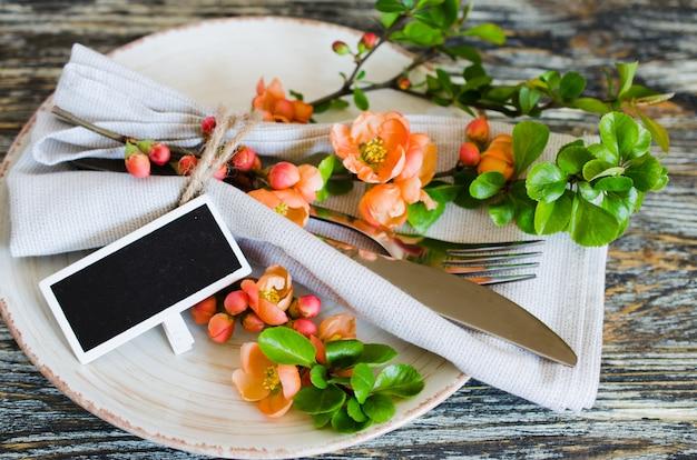 Винтажная сервировка с нежными цветами и тег на деревенском потертый стол. Premium Фотографии