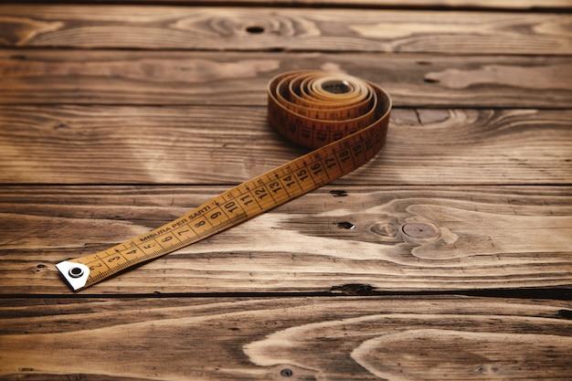 소박한 나무 테이블에 고립 된 압 연 빈티지 재단사 눈금자를 닫습니다. 무료 사진