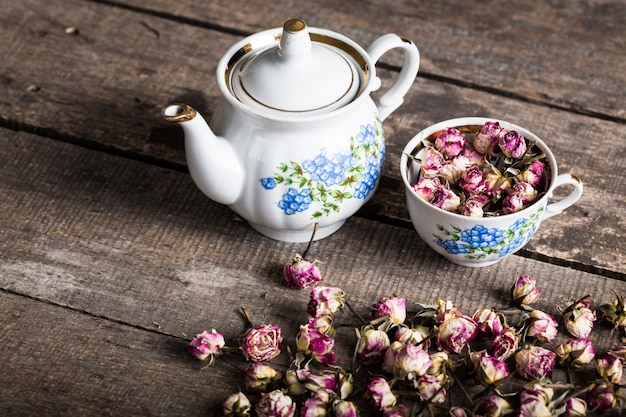 Vintage teapot and cup with blooming tea flowers on wood Premium Photo