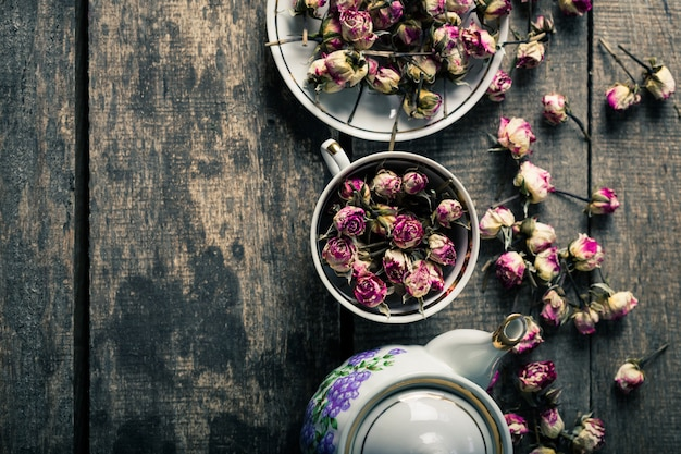 Vintage teapot and cup with blooming tea flowers on wooden background Premium Photo