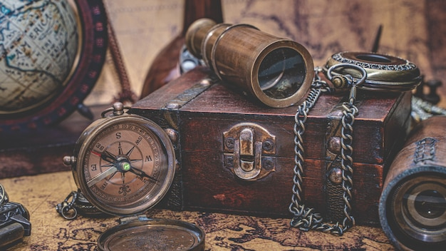 Vintage telescope, compass and old collection on treasure box Premium Photo