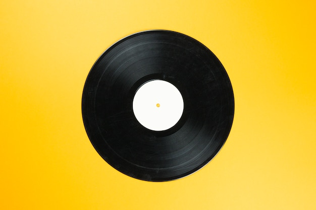 Vintage vinyl record disk with empty white label on orange background. retro sound technology to play music Premium Photo
