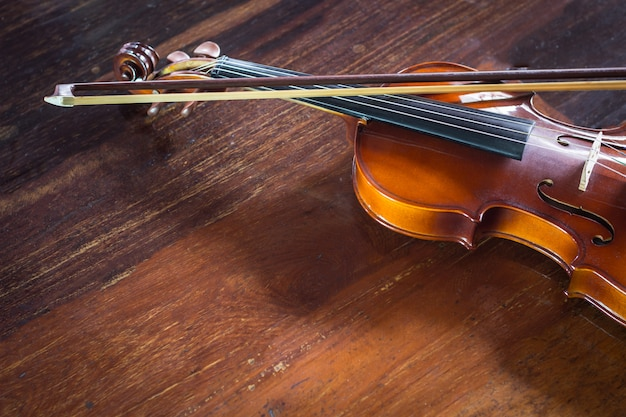 Vintage violin with bow on wood background, still life Premium Photo