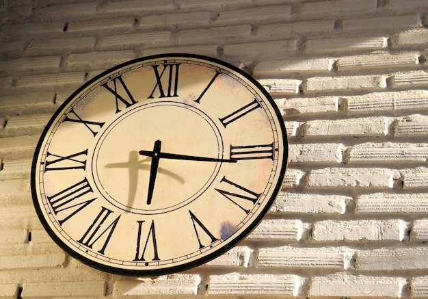 vintage wall clock on brickwall premium photo