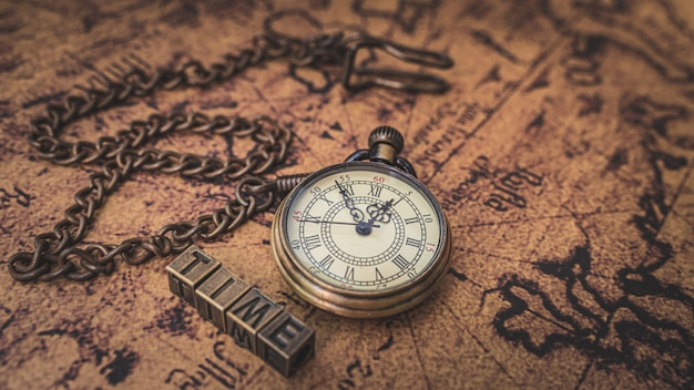 Vintage watch necklace on old world map Premium Photo