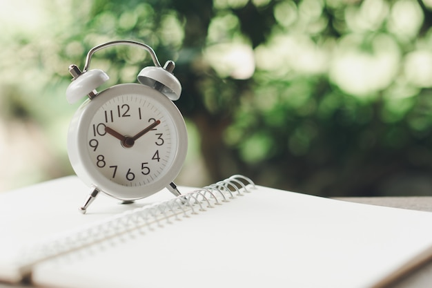 Vintage white alarm clock on on a notebook. it's time to rest. using as background Premium Photo