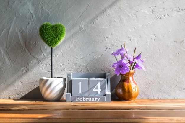 Vintage wood calendar for february 14 with green heart on wood table love and valentine's day concept background, backdrop. Premium Photo