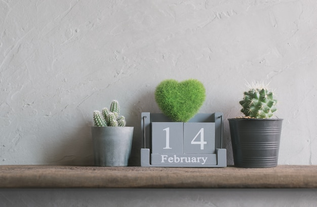 Vintage wood calendar for february 14 with green heart Premium Photo