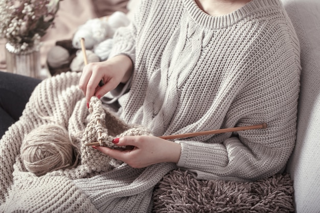 Vintage wooden knitting needles and yarn in woman's hands Premium Photo