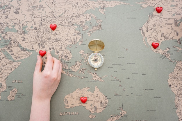 Vintage world map background with compass and hand placing red vintage world map background with compass and hand placing red hearts free photo gumiabroncs Gallery